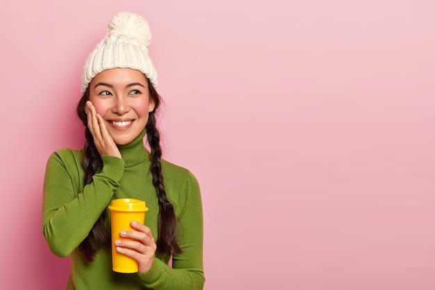 주름을 잡은 꿈꾸는 긍정적 인 십대 소녀, 뺨을 만지고, 커피 휴식 시간 동안 매우 즐거운 일을 기억하고, 테이크 아웃 음료를 들고, 겨울 모자와 녹색 폴로 넥을 착용하고, 장미 빛 벽 위에 포즈를 취합니다.