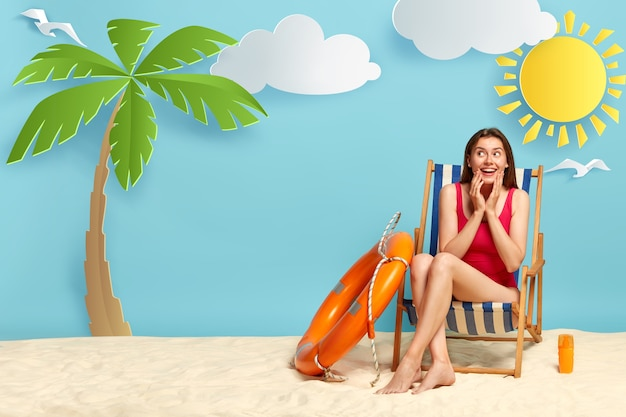 Dreamy positive woman enjoys hot day on coast, sits on deckchair, wears red bikini, uses suntan lotion to protect skin from sun
