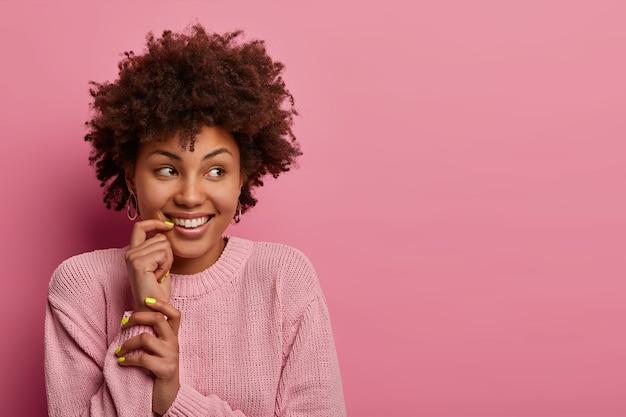 꿈꾸는 긍정적 인 여성은 옆으로 보이고 부드러운 미소, 하얀 치아가 있습니다.