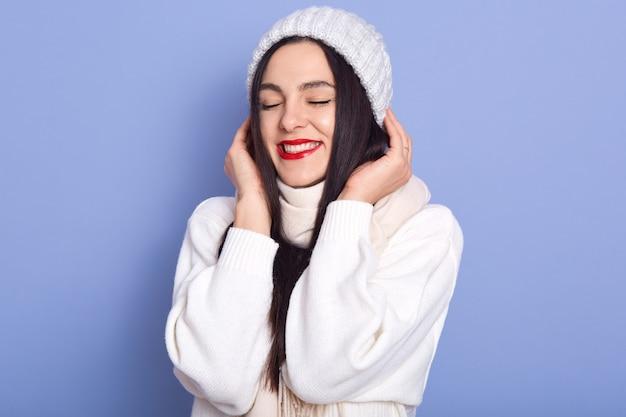 Dreamy pretty caucasian brunette young female wearing white warm sweater