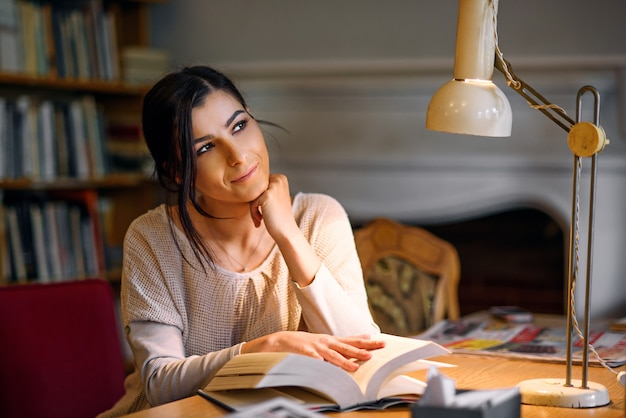 Dreamy pretty and enthusiastic student girl reading book in university library under a table lamp