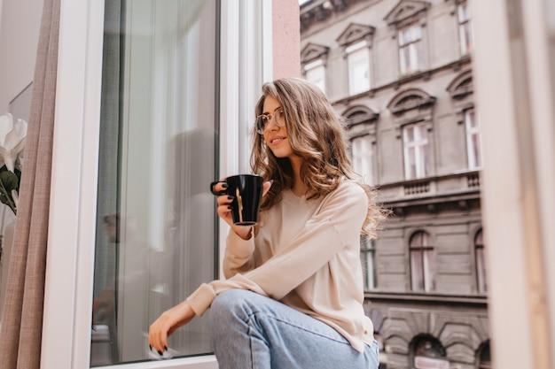 Dreamy pretty lady in blue jeans looking away, sitting beside window