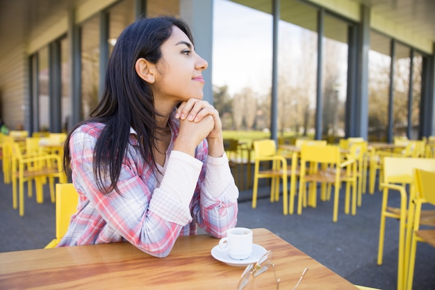 Dreamy pretty young lady enjoying drinking coffee in cafe