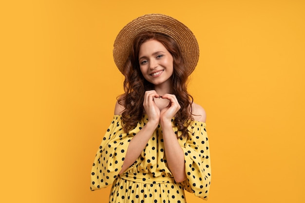 Мечтательная рыжеволосая женщина позирует в желтом платье с рукавами на желтом. летнее настроение.