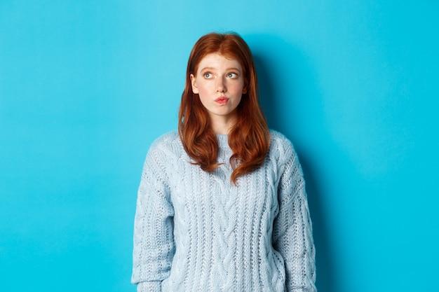 青い背景に立って、左上隅のロゴを見て、考えたり、決定を下す夢のような赤毛の女の子。