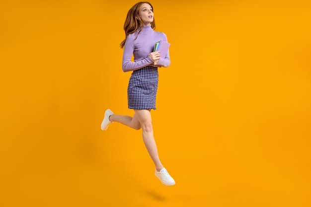 Dreamy redhead lady at weekend jumping, hold notebooks in hands on way home, in air, wearing casual shirt and skirt isolated yellow orange background. side view, copy space. full-length portrait