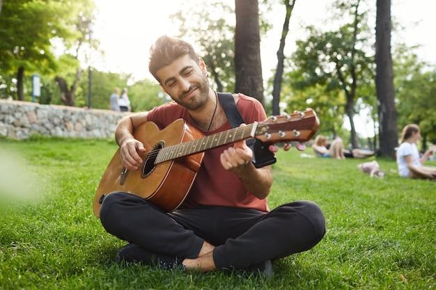 Мечтательный расслабленный мужчина играет на гитаре, сидит на траве в парке с инструментом