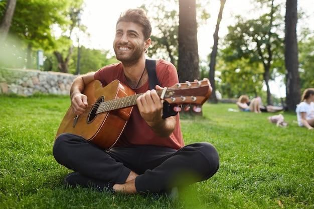 夢のようなリラックスした男がギターを弾いて、楽器のある公園の芝生の上に座る