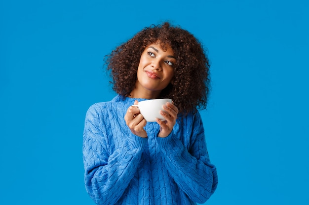 Dreamy, romantic and sensual lovely african-american woman, in sweater, tilt head and gazing distance, contemplate outside window beautiful snowy scenery, drinking hot tea, holding cup