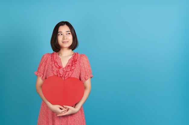 Dreamy, romantic young asian woman in red dress holds a large red paper heart and looks sideways