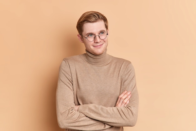 Dreamy satisfied blue eyed handsome male youngster stands crossed hands indoor looks into distance thinks about something pleasant wears casual beige turtleneck