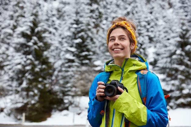 Una viaggiatrice europea soddisfatta e sognante tiene in mano la fotocamera digitale per fare foto, focalizzata a distanza