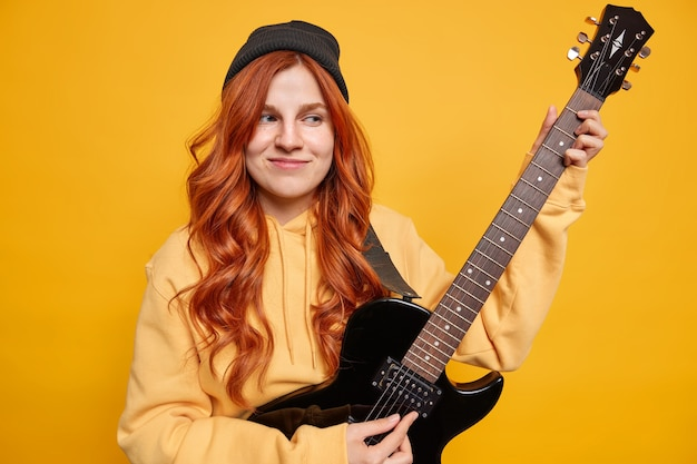 Dreamy satisfied female teenager musician plays electric guitar wants to become professional guitarist wears hoodie and hat has long red hair