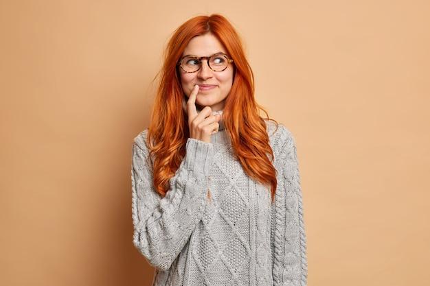 Мечтательная довольная рыжая женщина сосредоточенно держит указательный палец у уголка губ, задумчиво носит серый вязаный свитер.