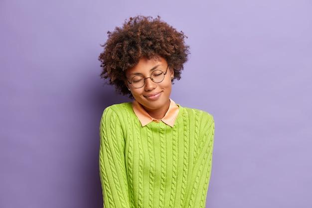 꿈꾸는 만족스러운 젊은 아프리카 계 미국인 여성이 눈을 감고 부드럽게 미소 짓습니다.