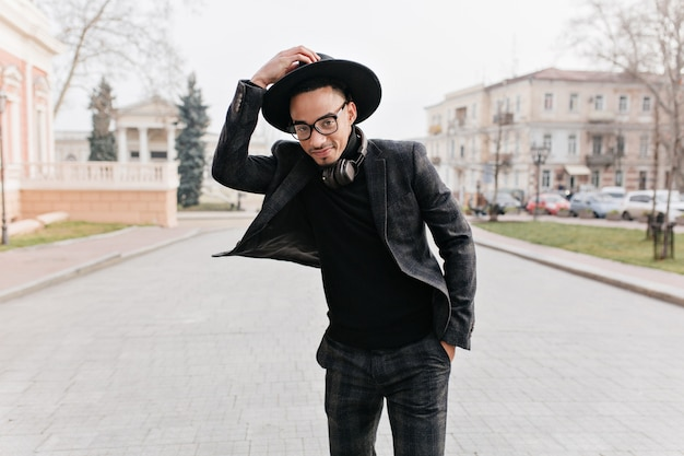 公園で喜んでポーズをとる市松模様のスーツを着た夢のようなスリムなアフリカ人。エレガントな服装で立っている笑顔の黒人少年の屋外の肖像画