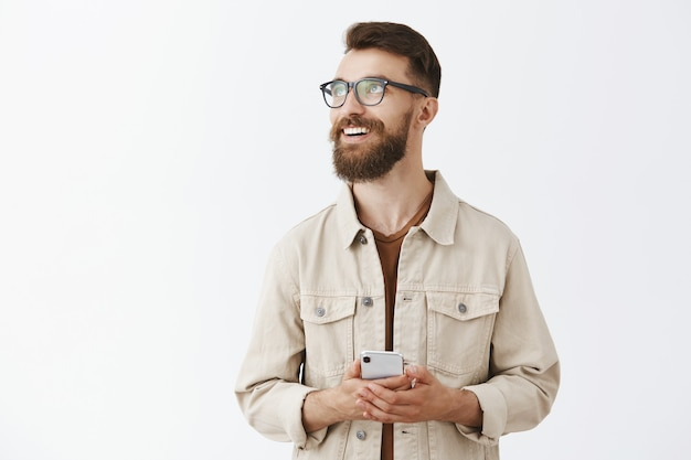 Dreamy smiling bearded man in glasses posing against the white wall
