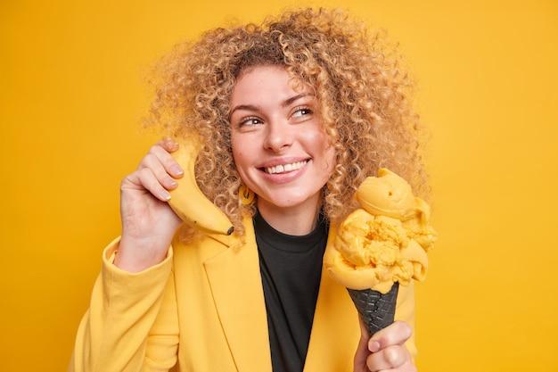 La donna dai capelli ricci sorridente sognante distoglie lo sguardo pensierosamente tiene il cono gelato mangia il dessert congelato tiene la banana vicino all'orecchio finge di parlare al telefono essendo di buon umore muro giallo
