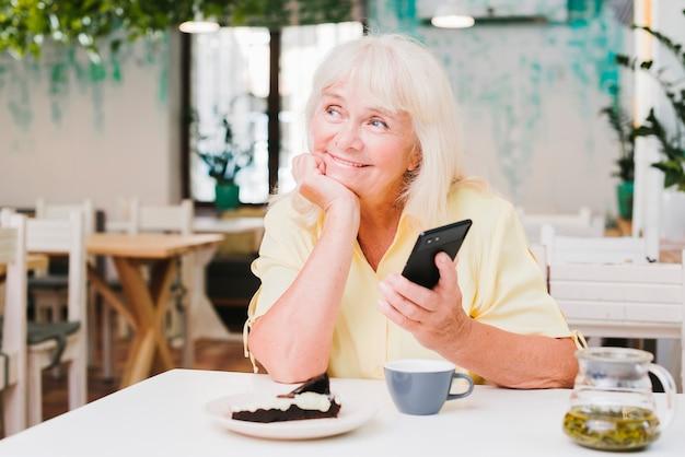 Мечтательная улыбающаяся пожилая женщина со смартфоном