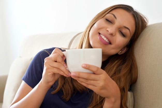 夢のような笑顔のポジティブな女の子の目を閉じて、ソファに座っていることを想像して暖かい飲み物とカップを保持します