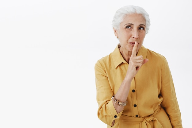 Мечтательная улыбающаяся старшая женщина шепчет и смотрит в левый верхний угол, делится секретом