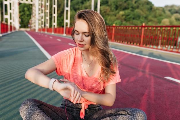 トレーニング後に時計を見ている夢のようなスポーティな女の子。スタジアムでマラソンの前にリラックスした洗練された女性の屋外ショット。