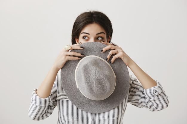 夢のようなスタイリッシュな女の子の帽子の後ろに顔を隠して左を覗く
