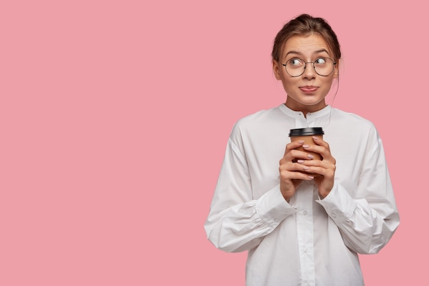 Giovane donna alla moda sognante con gli occhiali in posa contro il muro rosa