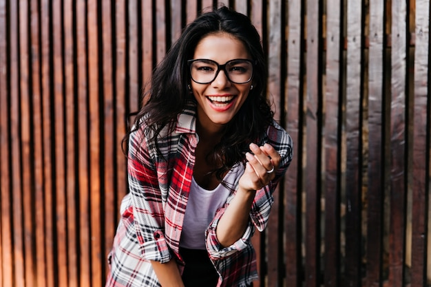 Modello femminile abbronzato sognante che posa emotivamente sulla parete di legno. il ritratto all'aperto della ragazza incantevole porta gli occhiali.