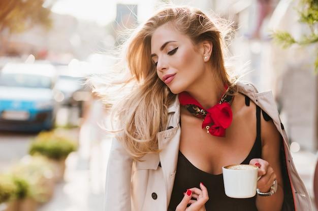 Ragazza abbronzata sognante in giacca marrone chiaro pensando a qualcosa con gli occhi chiusi e godersi la buona giornata. donna adorabile con una tazza di tè, trascorrere del tempo all'aperto al mattino.