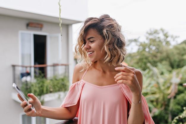 夢のような日焼けした女の子が笑顔で電話メッセージにテキストメッセージを送信します。ホテルのバルコニーに立ってスマートフォンの画面を見ている驚くべき巻き毛の女性モデル。