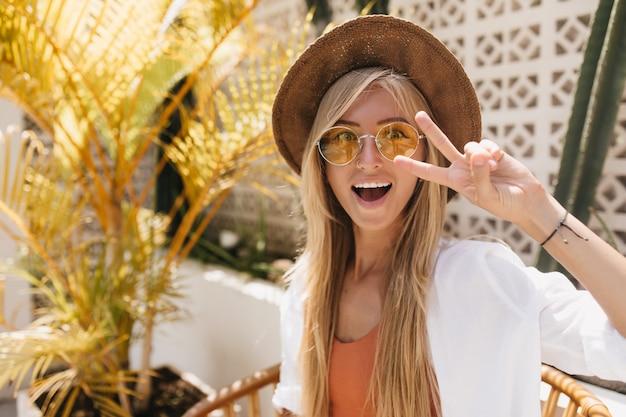 Мечтательная загорелая дама в желтых очках дурачится в курортном кафе. внешний портрет очаровательной белокурой девушки, позирующей с удивленной улыбкой.