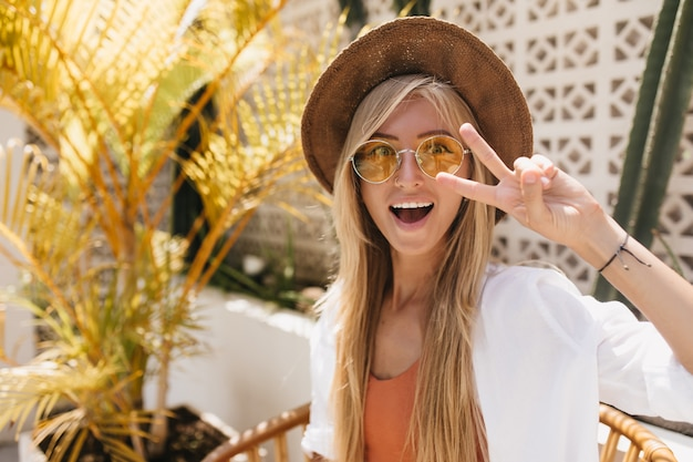 Dreamy tanned lady in yellow sunglasses fooling around in resort cafe. outdoor portrait of adorable blonde girl posing with surprised smile.