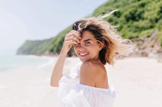 바다 해안에 서있는 동안 어깨 너머로보고 꿈꾸는 무두 질된 여자. 더운 날에 열 대 섬에서 기쁨과 함께 포즈를 취하는 사랑스러운 금발의 여자.