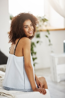 Dreamy tender african woman in sleepwear sitting on bed in morning smiling thinking.