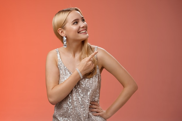 Dreamy tender attractive blond young woman in stylish silver shiny dress pointing looking upper right corner amused smiling broadly delighted see friend peek balcony, standing red background.