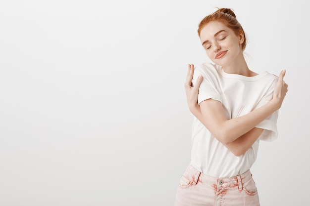 Dreamy tender redhead woman embracing own body, daydreaming