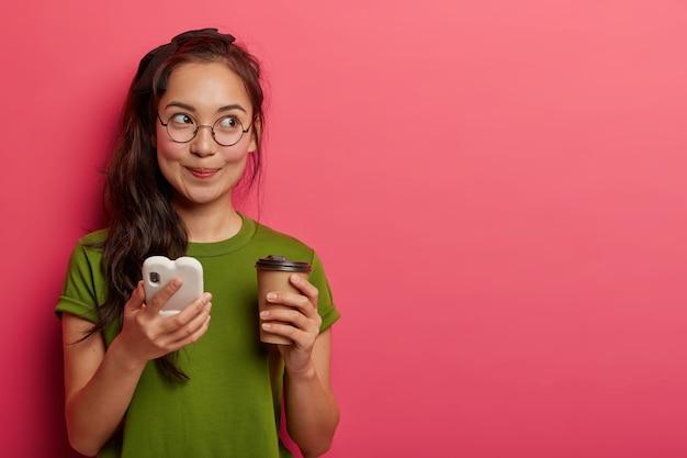 꿈꾸는 사려 깊은 여학생은 강의 후에 커피를 마시고, 현대적인 스마트 폰을 사용하고, 무언가를 생각하고, 외모를 꾸미고, 주문을 위해 온라인 애플리케이션을 사용합니다.