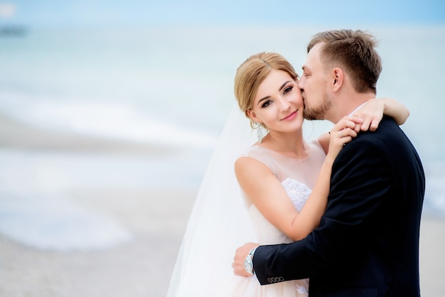 夢のような結婚式のカップルは、お互いを優しく立ててビーチに立つ