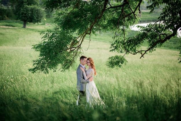 夢のウェディングカップルは背の高い草の中に立つ