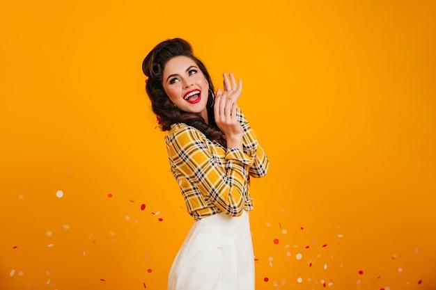 Signora ben vestita sognante che osserva in su. studio shot di accattivante pinup girl in posa su sfondo giallo.