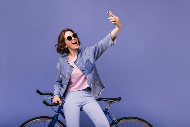 新しいバイクで自分撮りに電話を使用している夢のような白人の女の子。自転車の近くに立っているサングラスをかけた魅力的な巻き毛の女性。