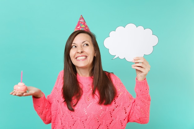 Dreamy woman in birthday hat looking up holding cake with candle, empty blank say cloud speech bubble for promotional content isolated on blue background. people lifestyle concept. mock up copy space.