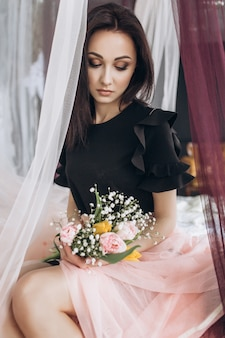 Dreamy woman in black dress sits on pink bed and holds bouquet on her knees