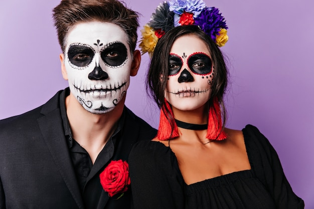 Dreamy woman in flower wreath posing in halloween with boyfriend. caucasian guys in zombie costumes standing on purple background.