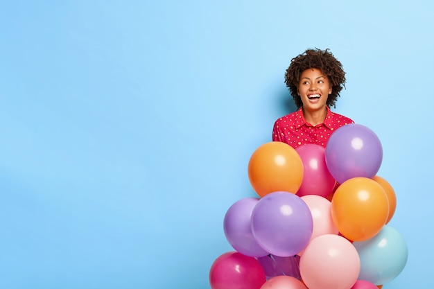Dreamy woman holds multicolored balloons while posing