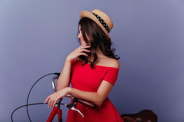 보라색 벽에 매력적인 미소로 포즈를 취하는 우아한 밀짚 모자에 꿈꾸는 여자. 자전거에 앉아 잠겨있는 갈색 머리 여성 모델.
