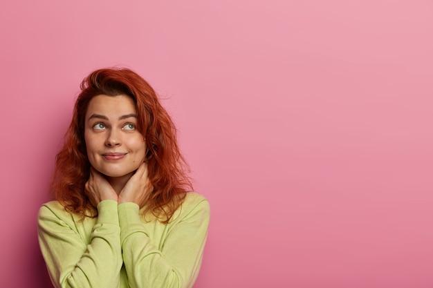 Мечтательная влюбленная женщина вспоминает идеальное свидание с парнем, думает о милых сладостях, держит руки на шее, куда-то смотрит, носит зеленый свитер