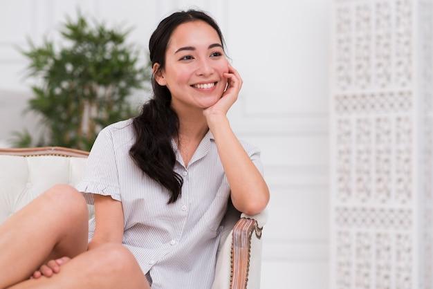 Мечтательная женщина в пижаме на диване