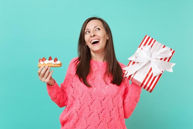 見上げるピンクのセーターの夢のような女性、エクレアケーキ、青い背景で隔離のギフトリボンと赤い縞模様のプレゼントボックスを保持します。バレンタイン、女性の日、誕生日の休日のコンセプト。コピースペースをモックアップします。